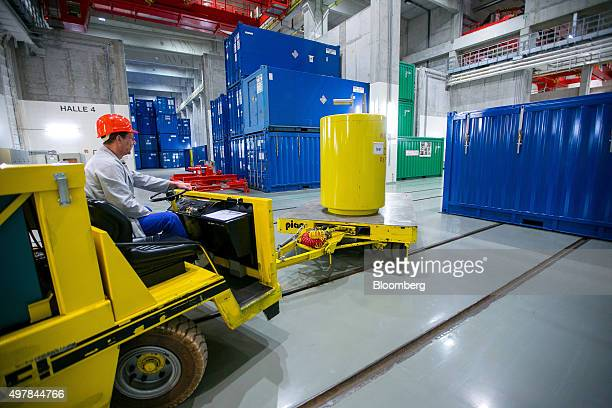 A worker drives a trailer vehicle to transport a container of radioactive waste into a temporary storage facility during decommissioning operations...