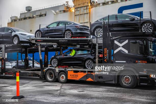 A worker drives an automobile produced by Tesla Inc onto a car transporter truck after arriving on the Glovis Courage vehicles carrier vessel at the...