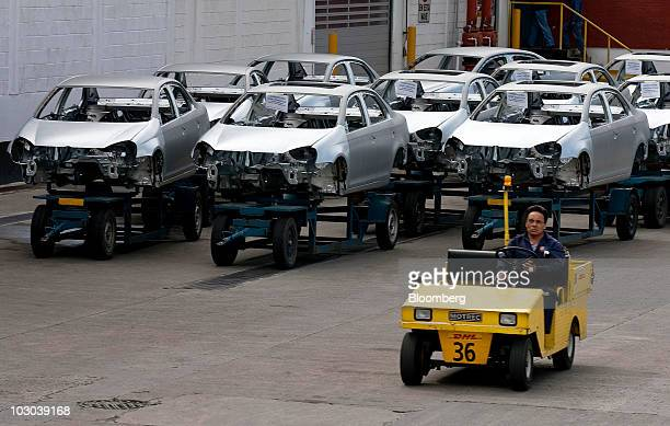 A worker drives past frames for Volkswagen AG's new Jetta compact sedan at the company's factory in Puebla Mexico on Thursday July 22 2010 The new...