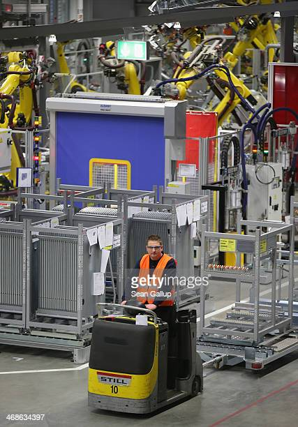A worker drives past robots welding the bodies of Porsche Macan SUVs at the heavily automated Porsche Macan factory at the Porsche plant on February...