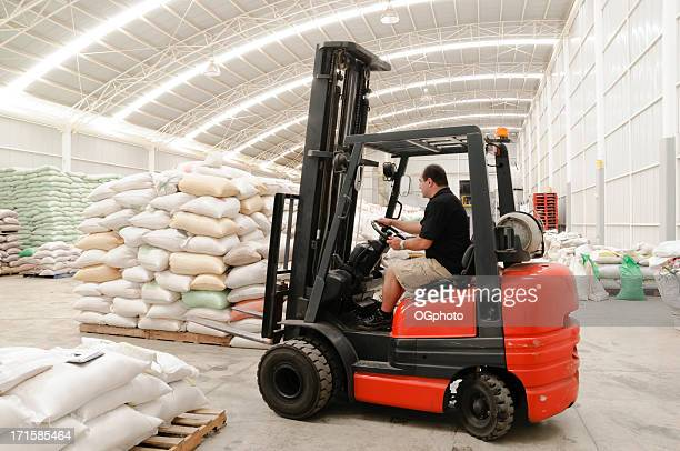 Worker driving a forklift in modern warehouse