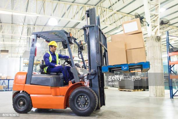 worker driving a forklift in warehouse - loading dock stock pictures, royalty-free photos & images