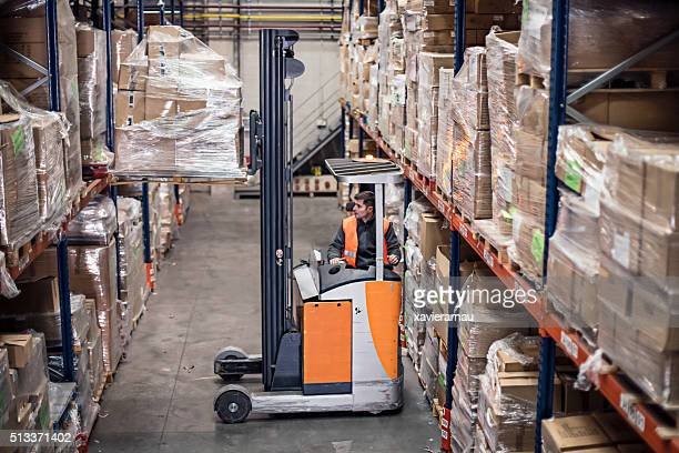 Worker driving a forklifts carrying cardboard box in warehouse
