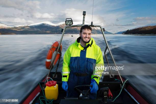 worker driving boat in rural lake - scotland stock pictures, royalty-free photos & images