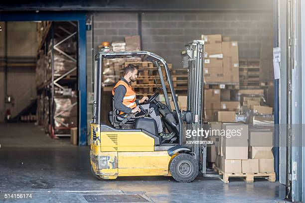 Worker driving forklift in warehouse