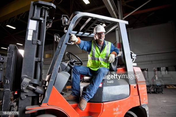 Worker driving forklift