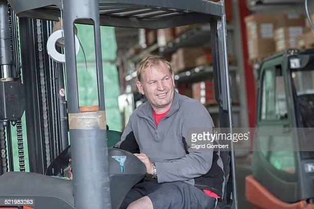 worker driving forklift truck in hardware store warehouse - sigrid gombert stock-fotos und bilder
