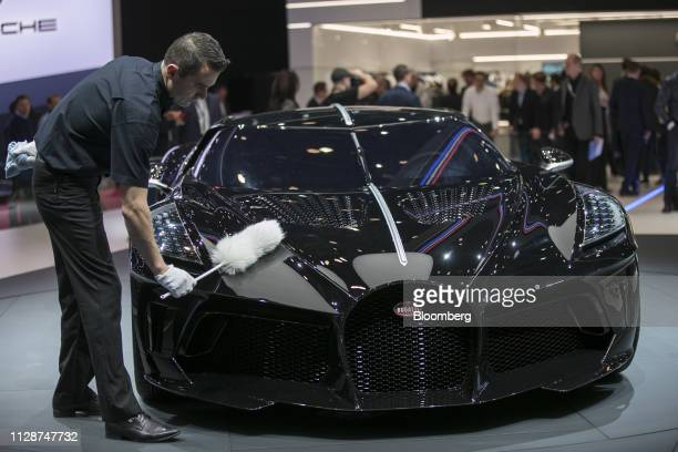A worker dusts the bodywork of a Bugatti Automobiles SAS La Voiture Noire ultra luxury automobile on display on the opening day of the 89th Geneva...