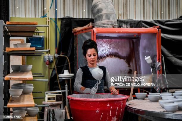Worker enamels ceramic bowls at Bordallo Pinheiro Factory in Caldas da Rainha on September 13, 2018. - Ignoring temporary walls which point to...
