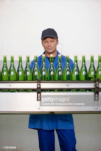 Worker examining bottles in factory