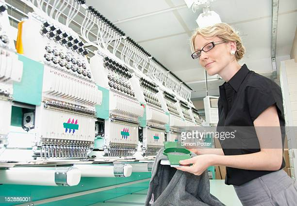 Worker examining fabric in factory