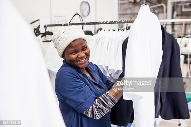 Worker examining shirt in garment factory