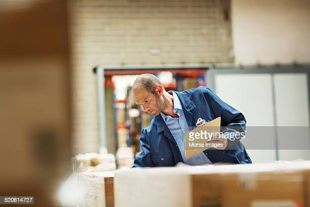 Worker examining stock in warehouse