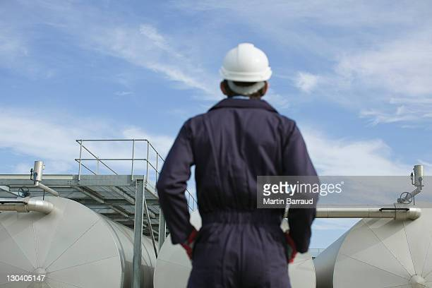 Worker examining tanks outdoors