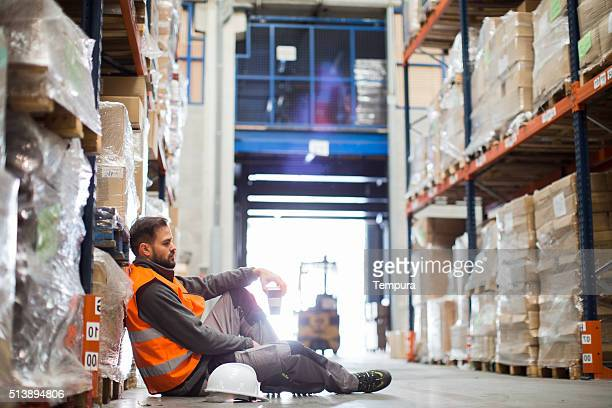 worker exhausted after a day's work resting in a warhouse. - overworked stock pictures, royalty-free photos & images