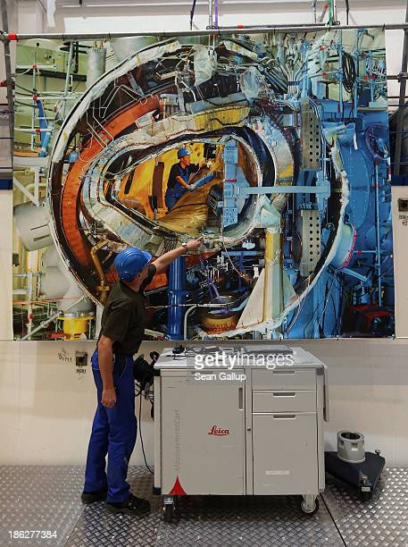 Worker explains a photo taken about a year and a half ago that shows construction of the interior plasma chamber of the Wendelstein 7-X experimental...