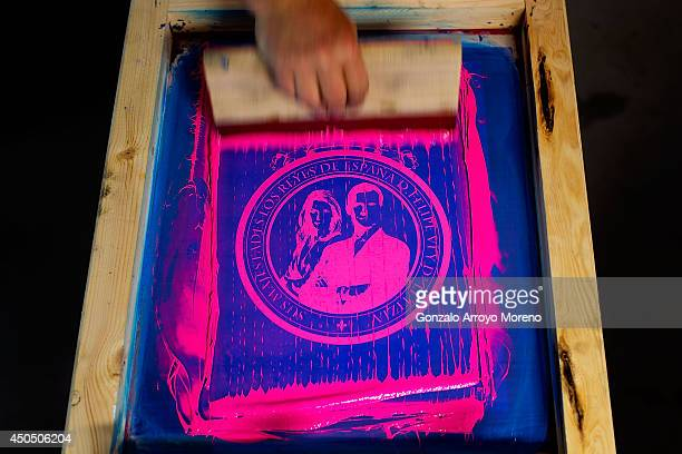 Worker extends paint on a serigraph machine doing a t-shirt of Prince Felipe and Princess Letizia as future Spanish monarchs of Spain at LK...