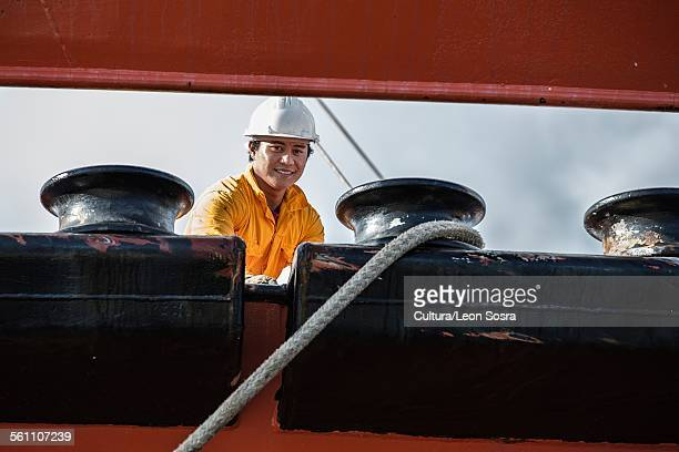 Worker fastening ropes to mooring posts on oil tanker
