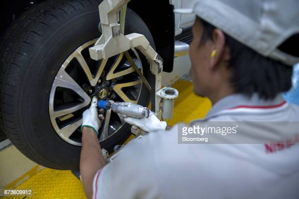 A worker fastens a wheel onto a Nissan Motor Co Navara pickup truck on an assembly line at the company's plant in Samut Prakan Thailand on Tuesday...