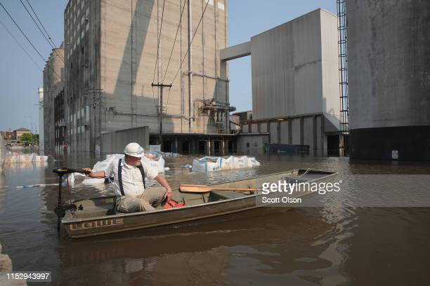 A worker ferries supplies through floodwater from the Mississippi River across Highway 100 to Ardent Mills on May 31 2019 in Alton Illinois The...