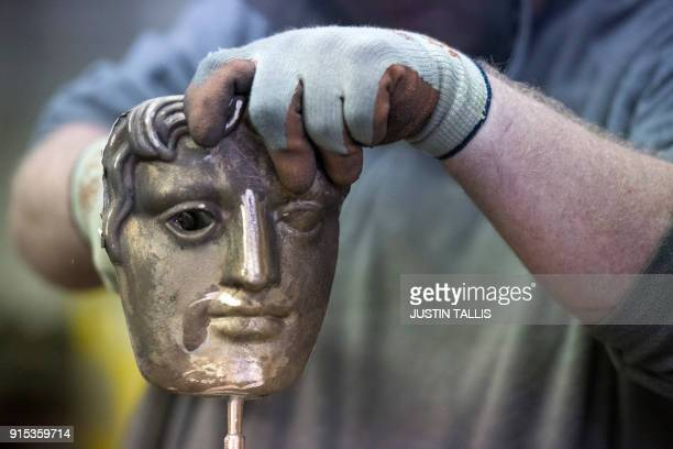 TOPSHOT A worker fettles a BAFTA mask during a photo call at the New Pro Foundries west of London on February 7 2018 ahead of the British Academy...