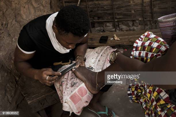 A worker files a customers toe nails during a pedicure near Bandim market in Bissau GuineaBissau on Tuesday Feb 13 2018 The International Monetary...
