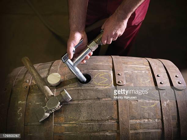 Worker filling whisky barrel in distillery
