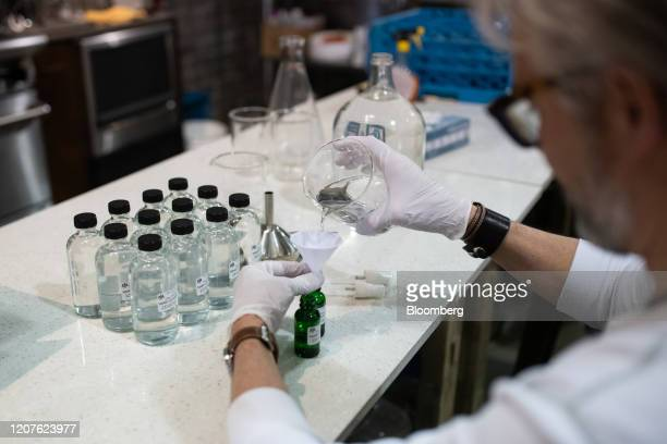 A worker fills a bottle with hand sanitizer solution made from distilled alcohol byproducts at the Glass Distillery in the SoDo neighborhood of...