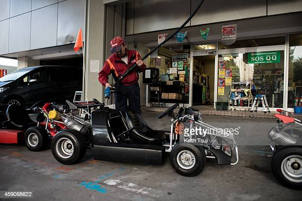 A worker fills a kart at the gas station for the Real Mario Kart event in Tokyo on November 16 2014 in Tokyo Japan The organizer calls for...
