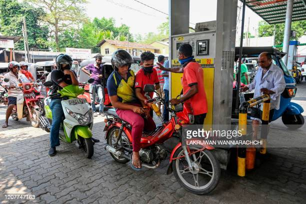 A worker fills the tank of a motorbike at a gas station after the authorities announced a weekend curfew in the country as a preventive measure...