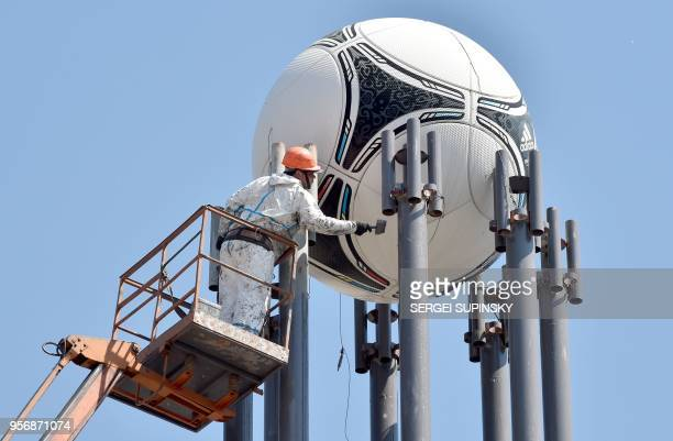 Worker finalises the painting of a street lamp where a football ball has been set up in the Ukrainian capital of Kiev, on May 10 2018, ahead of the...