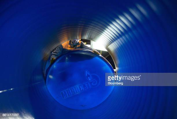 A worker fits a blue Gazprom PJSC branded end cap to a longitudinally welded large diameter steel pipe for use in oil and gas pipelines in a storage...