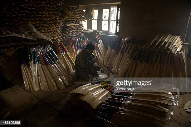 A worker fits a cover on cricket bats in a factory on February 10 2015 in Halmullah 50 km south of Srinagar the summer capital of Indian administered...