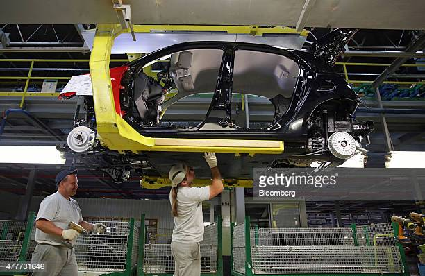 A worker fits a part to the chassis of a Renault Smart For Four automobile as it passes along the production line at the Renault Revoz dd plant a...