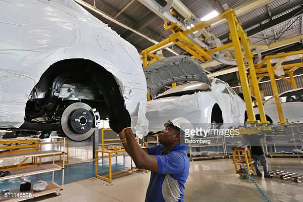 A worker fits parts to the underside of a raised Hyundai Motor Co Accent automobile on the production line at the Stallion Group vehicle assembly...
