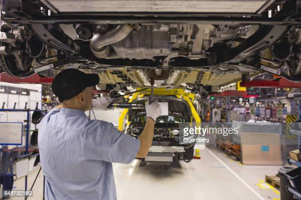 A worker fits parts to the underside of a raised Opel Astra automobile on the production line at the Opel automobile plant in Gliwice Poland on...