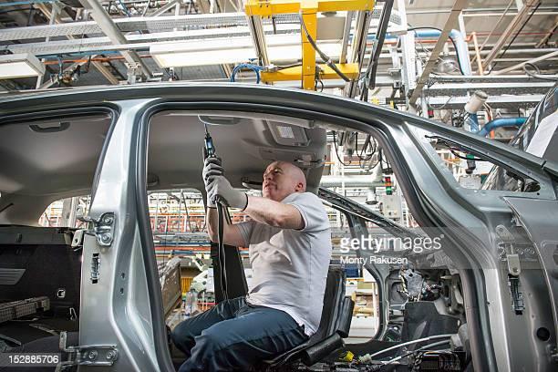 Worker fitting headliner in car in car factory