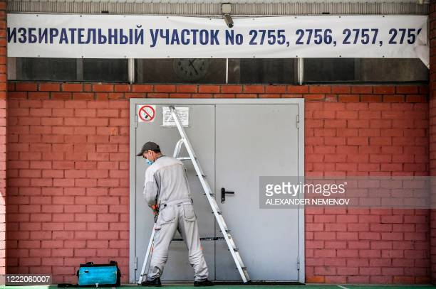 Worker fixes a banner at the entrance to a polling station in Moscow on June 23, 2020. - Russians will vote on July 1 on a series of constitutional...