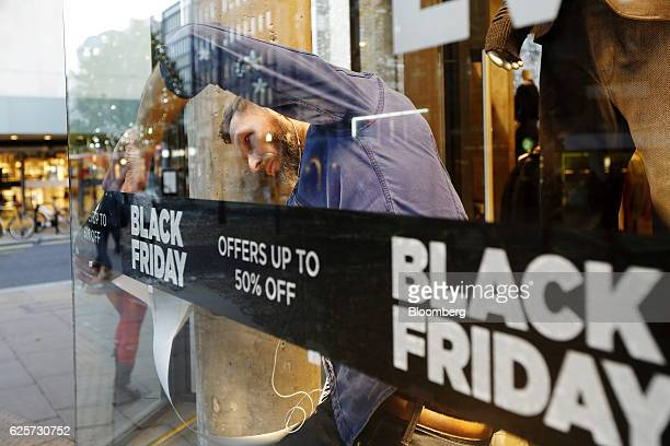 A worker fixes a Black Friday promotional sticker to a window at a GStar Raw Denim SL store on Oxford Street in London UK on Friday Nov 25 2016 Black...