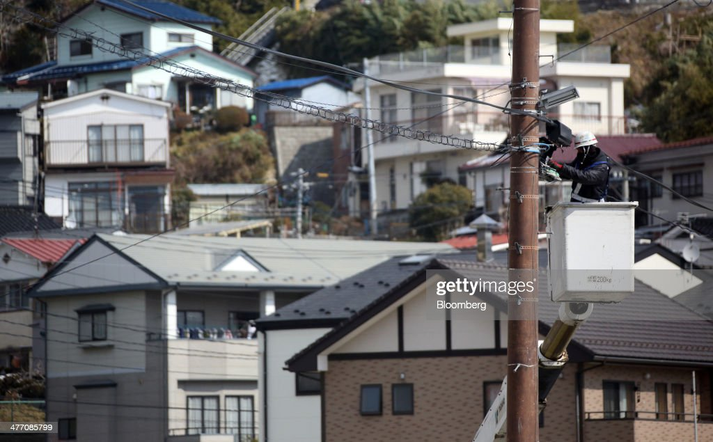 A worker fixes an utility cable in front of houses in Kesennuma City, Miyagi Prefecture, on Friday, March 7, 2014. Reconstruction of Tohoku, the northern Japan region devastated by the March 11, 2011 earthquake and tsunami, continues as the third anniversary of the disaster approaches. Photographer: Tomohiro Ohsumi/Bloomberg via Getty Images