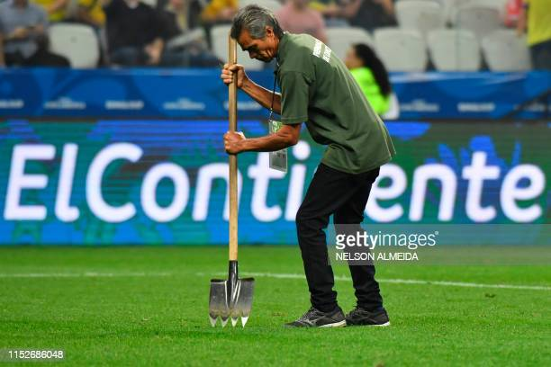 A worker fixes the grass of the field during halftime of the Copa America football tournament quarterfinal match between Colombia and Chile at the...