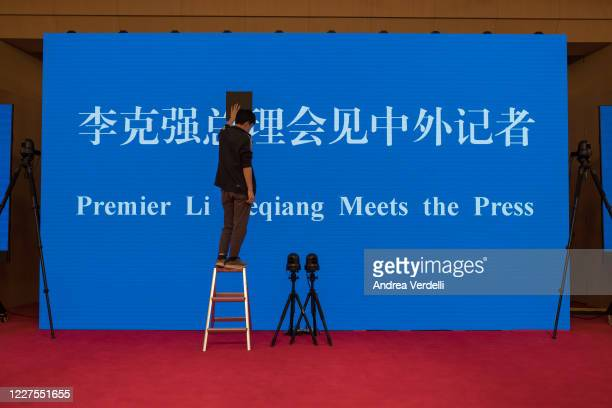A worker fixes the screen where the video press conference of Chinese Prime Minister Li Keqiang will be shown at the end of the National People's...