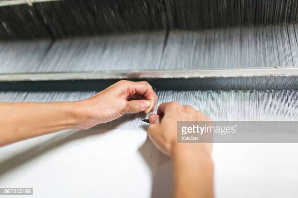 worker fixing the wrong thread in the weaving machine - loom stock pictures, royalty-free photos & images