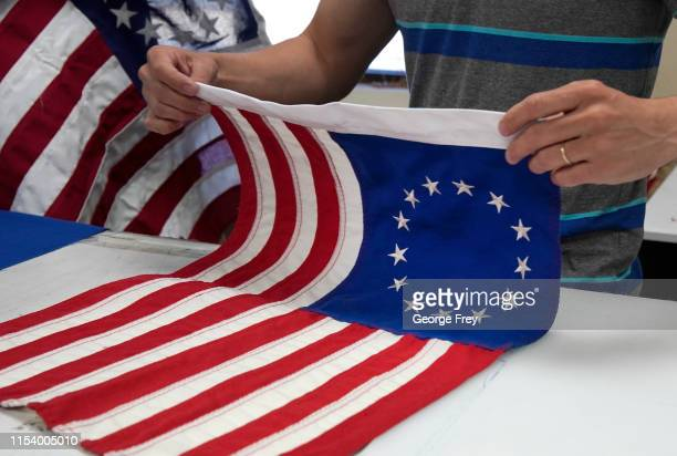 A worker folds a newly made Betsy Ross flag made out of fire proof material at Colonial Flag on July 5 2019 in Salt Lake City Utah The Betsy Ross...