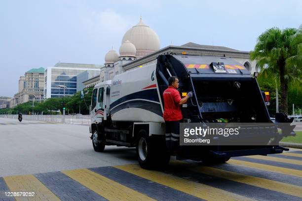 A worker for Alam Flora Bhd rides on the back of a garbage truck travelling along a road near the Palace of Justice in Putrajaya Malaysia on...