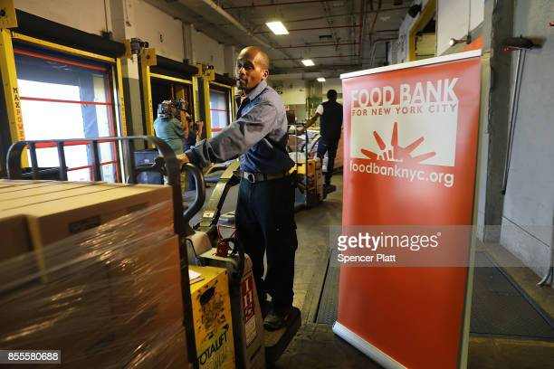 A worker for the Food Bank For New York City moves a pallet of food headed to needy Americans in hurricane ravaged Puerto Rico on September 29 2017...