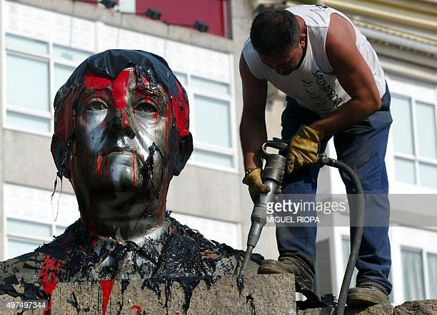 A worker frees with a drill a bust of Spanish dictator Francisco Franco from its plinth prior its removal in the central square of the Spanish...