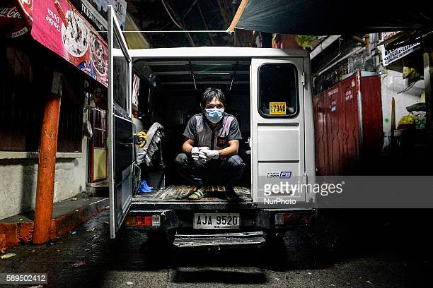 A worker from a funeral parlor sits on the back of an ambulance while waiting to collect the corpse of a suspected drug pusher who was shot dead...