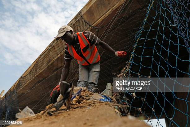 A worker from Freshngo removes plastic deluge from litter trap nets and long line cables that was washed down under a bridge on the Clayville...