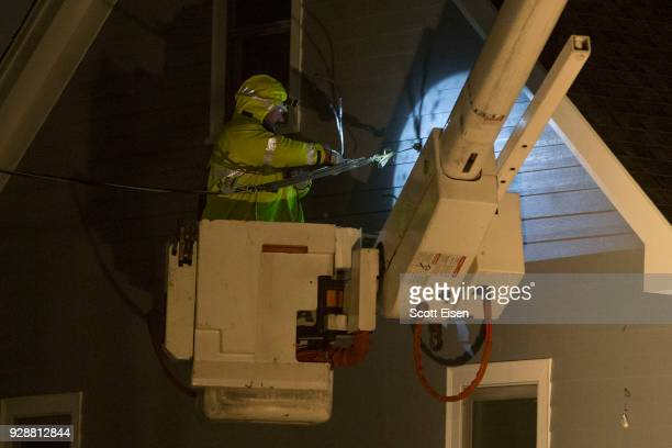 A worker from National Grid reattaches a downed highpower line on Landgrane St on March 7 2018 in Quincy Massachusetts Large portions of the East...